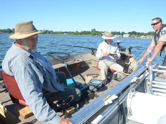 Deputy Dave Winder checks with fishermen, Ken Vandecar, left, and Larry Carter.