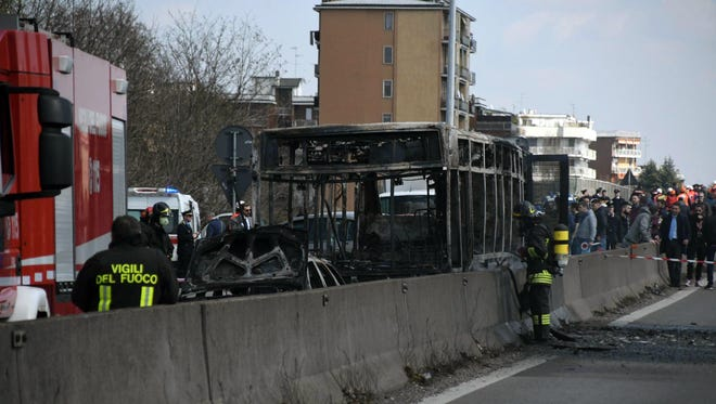 Firefighters stand by the gutted remains of a bus in San Donato Milanese, near Milan, Italy, March 21, 2019.