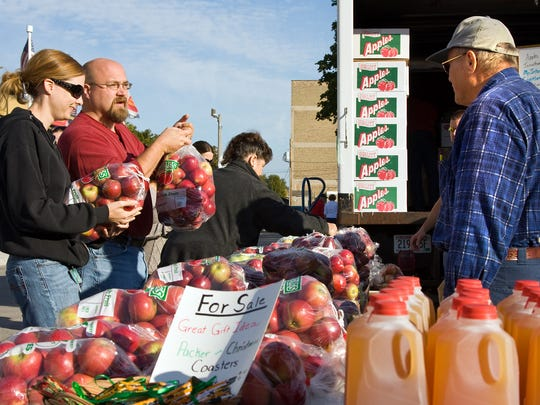 In this file photo, Heather Donati (from left) and Joe Donati of Two Rivers purchase fresh apples from Bob Butzer of Hillside Apples, Casco, during Apple Fest in Two Rivers.