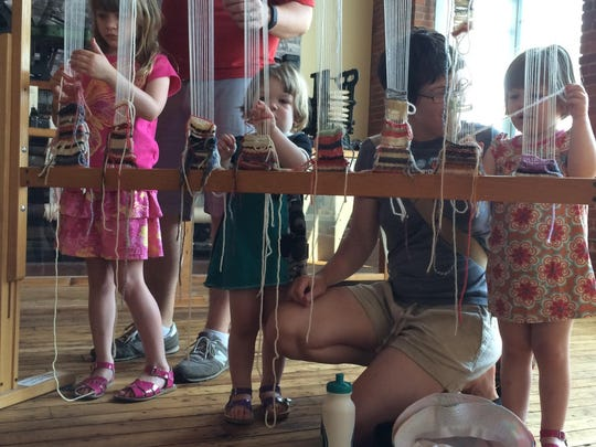 Hands-on history: The Blend-Montague family of Winooski explores a weaving display on Saturday at the downtown Heritage Mill Museum during a previous French Heritage Day. From left: Alexis Blend, 8; Luke Montague, Juniper Montague, 2; Charlotte Blend and Adelaide Montague, 2.