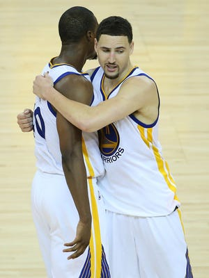 Golden State Warriors forward Harrison Barnes (40) and guard Klay Thompson (11) celebrate the 108-100 victory against the Cleveland Cavaliers following the overtime period in game one of the NBA Finals at Oracle Arena.