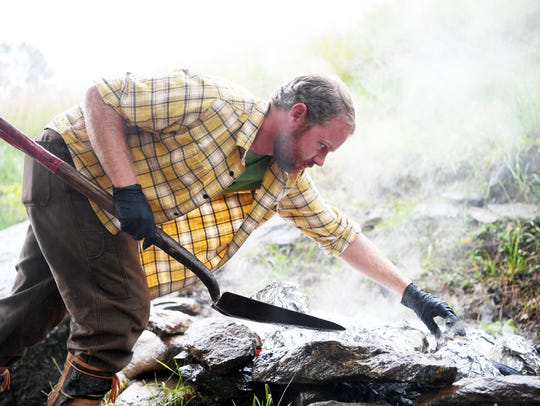 Michael Rayburn removes pumpkins from a fire at Rayburn