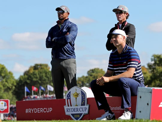 Woods and Team USA player Jordan Spieth watch on the