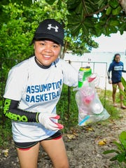 Lia Manlutac, 13, shows a sampling of the litter she and fellow student athletes from the Philippines' Assumption Antipolo school have collected along the shore of Ypao Beach in Tumon on Wednesday, Oct. 28.