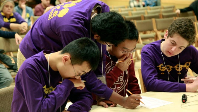Larry Chen, Suhaas Narayanan, Nathan Sima, and Antonio Izzo, of Fort Collins High School, collaborate on a group question. The team won a regional competition and will go on to compete in the National Ocean Science Bowl later this month.