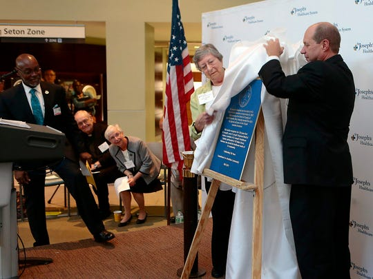 Sister Marilyn Thie, board chair of St. Joseph's Health, and Kevin Slavin, its president and CEO, unveil a historic marker that was placed at the site of the original hospital in Paterson to mark the hospital's 150th anniversary last year.