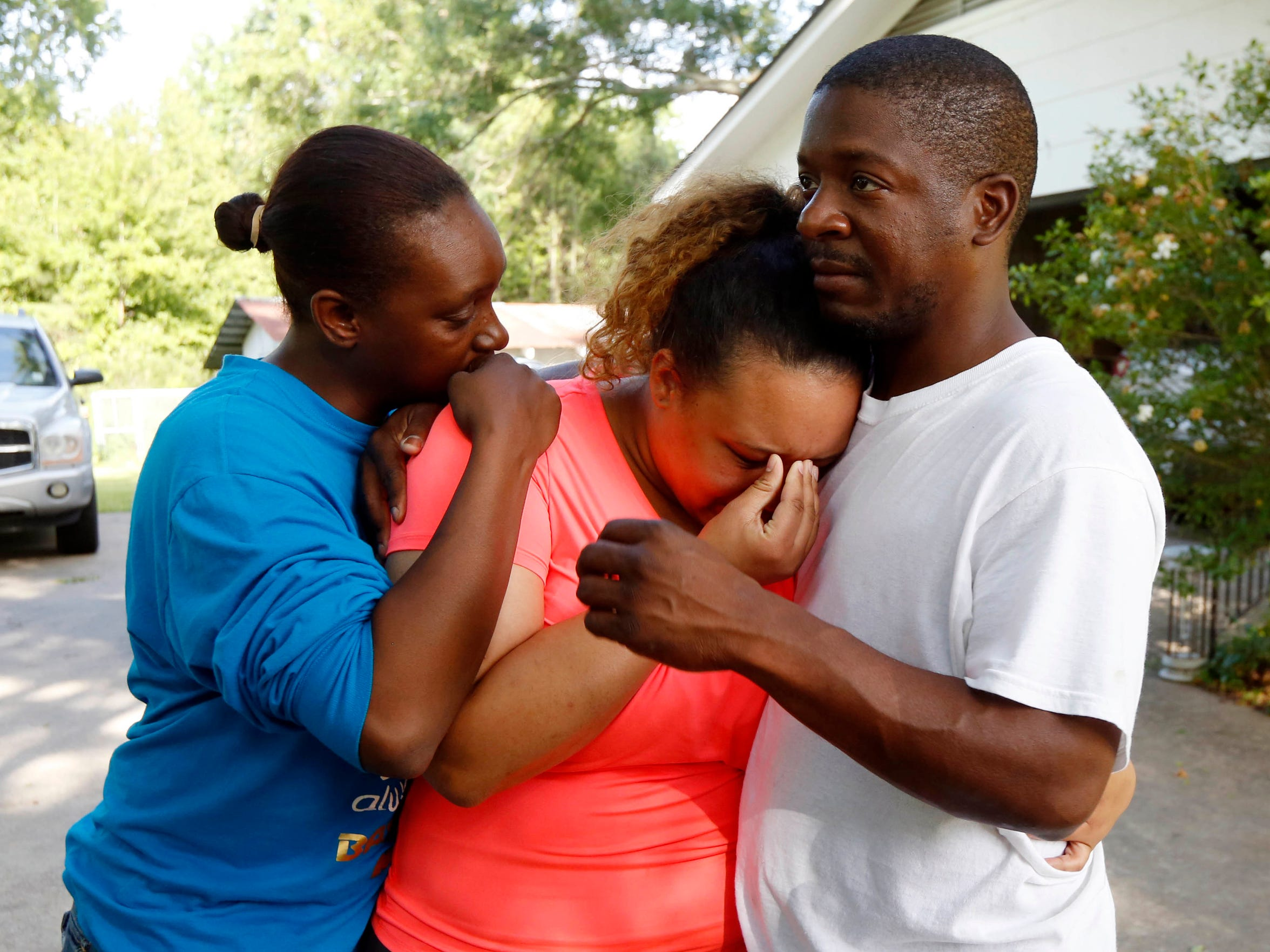 Christianna May-Kelly, center, is supported by family members as she cries after answering reporters questions outside her parents' home in Brookhaven, Miss., Sunday, May 28, 2017. May-Kelly said her parents and mother were among the people gunned down during a shooting in rural Mississippi Saturday night.