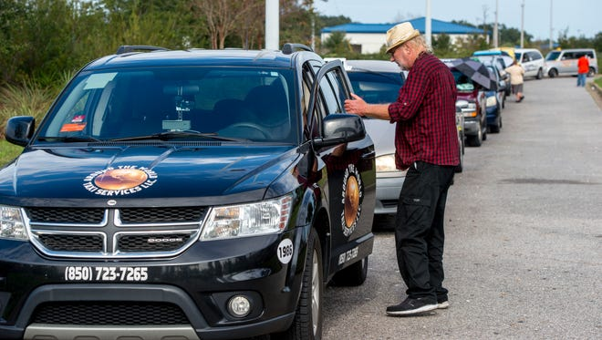 Taxi driver Elton Briley waits for a customer in the cab queue Tuesday at the Pensacola International Airport. Ashton Hayward says he will extend an agreement to allow Uber drivers to wait for passengers near the airport, but not on airport property, beyond the original February 11 deadline.