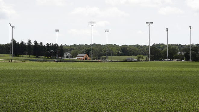 Light stands from a baseball field being built near the Field of Dreams movie site, rear, are seen, Friday, June 5, 2020, in Dyersville, Iowa. Major League Baseball is building the field a few hundred yards down a corn-lined path from the famous movie site in eastern Iowa but unlike the original, it's unclear whether teams will show up for a game this time as the league and its players struggle to agree on plans for a coronavirus-shortened season.