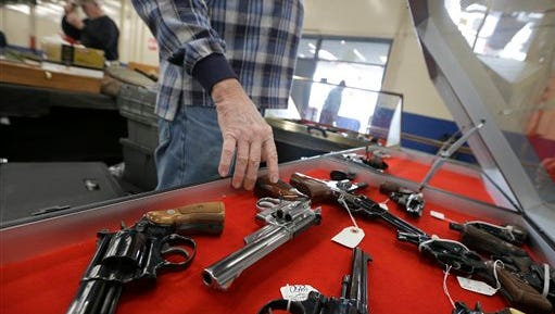 A dealer arranges handguns in a display case before a show at the Arkansas State Fairgrounds in Little Rock, Ark. A major U.S. trend survey finds that the number of Americans who live in a household with at least one gun is lower than it's ever been. That the number of households with at least one gun is declining doesn't necessarily mean that the number being purchased is on the decline. Data from the FBI's National Instant Criminal Background Check system shows that in recent years there's actually been an increase in the number of background checks being run, suggesting the total number of firearms being purchased is going up.