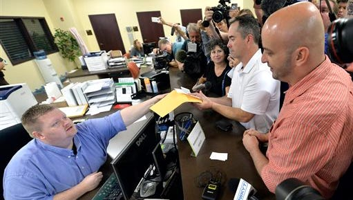Rowan County deputy clerk Brian Mason, left, hands James Yates, and his partner William Smith Jr., their marriage license at the Rowan County Judicial Center in Morehead, Ky., Friday, Sept. 4, 2015. After four attempts, Yates and Smith were finally issued their marriage license. (AP Photo/Timothy D. Easley)
