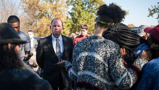 In a Nov. 3, photo, University of Missouri President Tim Wolfe speaks with members of Concerned Student 1950 senior DeShaunya Ware, right, and junior Shelbey Parnell, center, as they call for Wolfe's resignation outside University Hall in Columbia, Mo. Wolfe resigned Monday, Nov. 9, amid criticism of handling of racial issues.