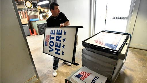 """Dusty DeVinney places """"vote here"""" signs onto a cart as he loads election materials at the Willowbank building Monday, April 25, 2016, in Bellefonte, Pa., in preparation for the primary election. For the first time in many years, Democrats and Republicans in Pennsylvania picked presidential candidates in a meaningful primary.They'll help make the decision in the presidential race -- and plenty of state and local races -- on Nov. 8."""