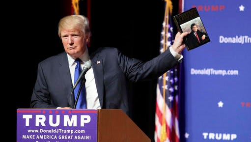 """FILE - In this Aug. 19, 2015 file photo, Republican presidential candidate Donald Trump holds up a copy of his 1987 book, """"Trump: The Art of the Deal"""" during his campaign town hall event at Pinkerton Academy in Derry, N.H. Trump's first book is a memoir/manifesto dedicated to a life of big-time negotiating."""