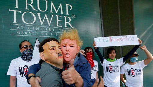 "Protesters, one wearing a Donald Trump mask and another with an Adolf Hitler mask, embrace as others display a #lovetrumpshate hashtag during a brief picket at the Trump Tower hours after Trump was sworn in as the 45th President of the United States Saturday, Jan. 21, 2017 in the financial district of Makati city east Manila, Philippines. Pledging emphatically to empower America's ""forgotten men and women,"" Donald Trump was sworn in as President of the United States on Friday, taking command of a riven nation facing an unpredictable era under his assertive but untested leadership."