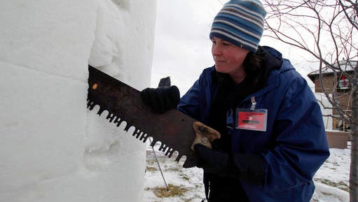 In this Wednesday, Feb. 1, 2017, photo, snow sculptor Gina Diliberti works on her team's piece for the the U.S. National Snow Sculpting Championship in Lake Geneva, Wis. Sculpting began Wednesday with judging set for Saturday morning along Geneva Lake.