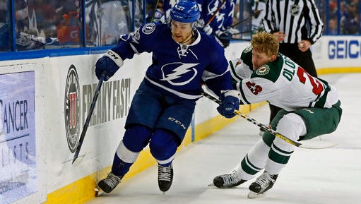 Tampa Bay Lightning's Jonathan Drouin tries to avoid the check of Minnesota Wild's Gustav Olofsson, of Sweden, during the second period of an NHL hockey game Thursday, March 9, 2017, in Tampa, Fla.