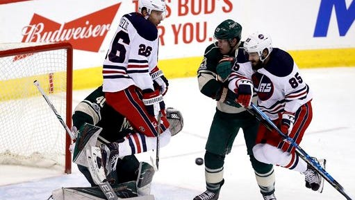 Winnipeg Jets' Blake Wheeler (26) and Mathieu Perreault (85) both jump over a shot while screening Minnesota Wild goaltender Devan Dubnyk (40) with Wild's Ryan Suter (20) in front of the net during the first period of an NHL hockey game in Winnipeg, Manitoba, Sunday, March 19, 2017.