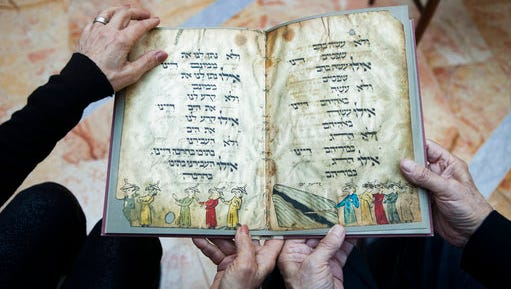 File - In this file photo taken Wednesday, April 13, 2016, Eli and Shuli Barzilai hold a copy of the Birds' Head Haggadah, the text read around Jewish dinner tables on the Passover holiday, in their home in Jerusalem. Last year, the descendants of German Jewish lawmaker Ludwig Marum requested the Israel Museum pay compensation for the famed Bird's Head Haggadah. They say the Haggadah was snatched from their grandfather's family after he was rounded up by the Nazis and later sold to the predecessor of the Israel Museum in Jerusalem without their consent.
