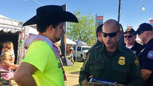 In this April 6, 2017 photo, a U.S. Border Patrol agent gives information about working for the agency to 24-year-old Ric Kindle, of the Phoenix area, at the Country Thunder Music Festival in Florence, Ariz. U.S. Customs and Border Protection, the parent agency of the Border Patrol and of Office of Field Operations, set up the recruitment booth at the festival in an effort to hire more agents and customs officers. President Donald Trump has ordered 5,000 new Border Patrol positions.