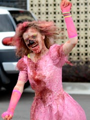 Guinevere Allen, 12, who likes to be called Guinufear, dances at the Milan Zombie Walk in downtown Milan Saturday. Walkers were encouraged to bring cans of food for the Feeding America Backpack Program.