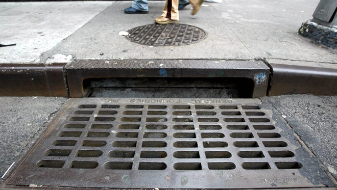 Pedestrians walk by a sewer grate.