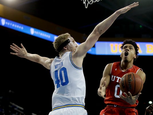 Utah guard Sedrick Barefield, right, shoots around UCLA center Thomas Welsh during the first half of an NCAA college basketball game in Los Angeles, Thursday, Jan. 11, 2018. (AP Photo/Chris Carlson)