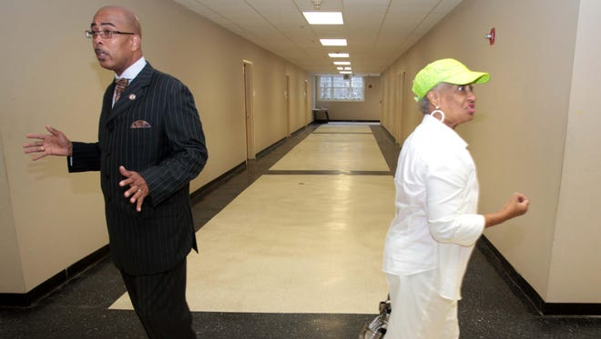 Monroe City School Board President Rodney McFarland and Brenda Shelling, board vice-president, move in opposite directions as they tour the basement at Neville High School in July.