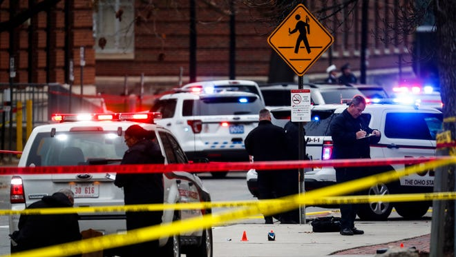In this Nov. 28, 2016, file photo, crime scene investigators collect evidence from the pavement as police respond to an attack on the Ohio State University campus. Franklin County, Ohio, Prosecutor Ron O'Brien announced Wednesday, May 3, 2017, that a grand jury has cleared Alan Horujko, the Ohio State University Police officer who fatally shot the man responsible.
