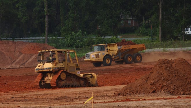Construction crews grade the site in preparation for the new distribution center that will serve FedEx Ground.