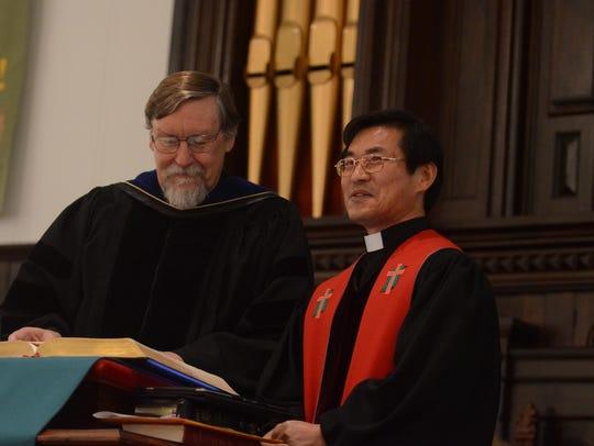 Reverend Sun Jong Ju, right, provides October 21's