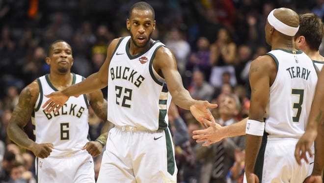 Khris Middleton celebrates with Bucks teammates Eric Bledsoe (left) and Jason Terry (right) after scoring two of his 35 points Monday night in their victory over the Suns.