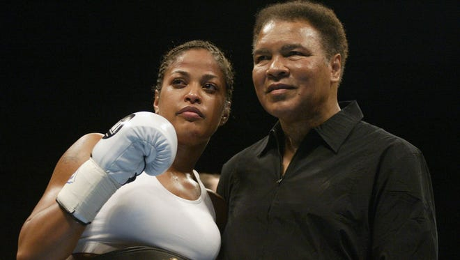 Boxer Laila Ali poses with her father, former heavyweight champion Muhammad Ali, after she defeated Suzy Taylor in two rounds at the Aladdin Casino in Las Vegas, Nevada, August 17, 2002.