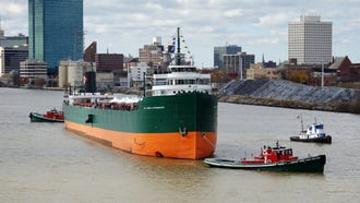 On Oct. 27, 2012, the historic Great Lakes freighter S.S. Col. James M. Schoonmaker is tugged on the Maumee River past the Toledo skyline to its new mooring at the National Museum of the Great Lakes.