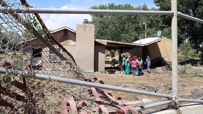 Family members and friends gather at the site of one of the damaged homes in the Salt Creek Wash area of north Shiprock on Aug. 6.