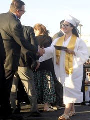 Ashley Altemeyer shakes hands with Deputy Superintendent Alan Reeder after accepting her diploma.