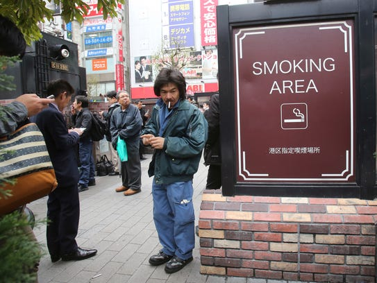 People gather at a smoking area in Tokyo on  April