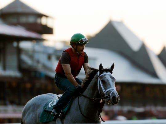 An exercise rider rides a horse during morning workouts at Saratoga Race Course on Thursday, July 17, 2014, in Saratoga Springs, N.Y. The Saratoga horse racing meet opens on Friday. (AP Photo/Mike Groll)