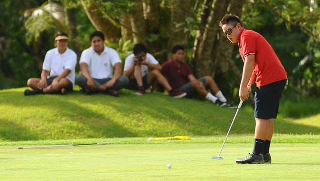 Brentt Salas putts for the hole during the Independent Interscholastic Athletic Association of Guam Golf League match at the Guam International Country Club in Dededo on Thursday, Sept. 10, 2015.