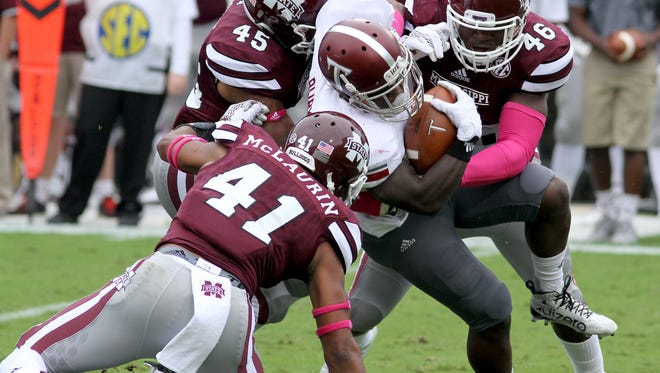 Mississippi State defensive players, including Mark McLaurin (41), J.T. Gray (45 and Dezmond Harris (46), wrap up Troy running back Brandon Burks during the first half of an NCAA college football game in Starkville, Miss., Saturday, Oct. 10, 2015. (AP Photo/Jim Lytle)