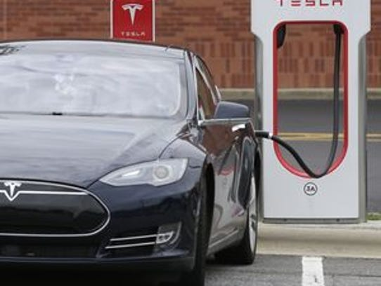 A Tesla is recharged at a station at the Cochran Commons