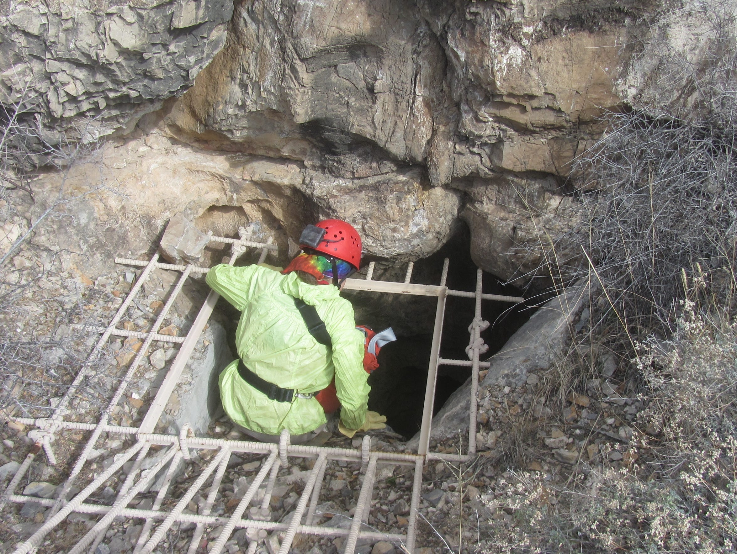 A caver prepares to enter an underground cave. Those going spelunking should wear a hard hat with a chin strap and bring durable clothes and boots, as well as gloves and several light sources.