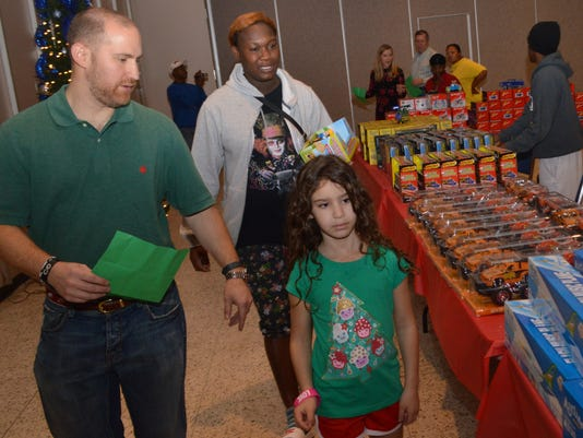 ANI Doll and Toy Distribution Alexandria Rotary Club member Brad Kirzner (front, left) and daughter Camille Kirzner (front, right) help Chantal Green (back, center) look for Christmas gifts for her sons Jaylen Fortson and Jaqwain Casson at the Doll & Toy Fund Distribution held Saturday, Dec. 21, 2013 at Alexandria Convention Hall in downtown Alexandria. The Town Talk and Alexandria Rotary Club are co-sponsors of the Doll & Toy Fund. The Salvation Army, Shepherd Center and Volunteers of America provide names of children for the fund.-Melinda Martinez/mmartinez@thetowntalk.com