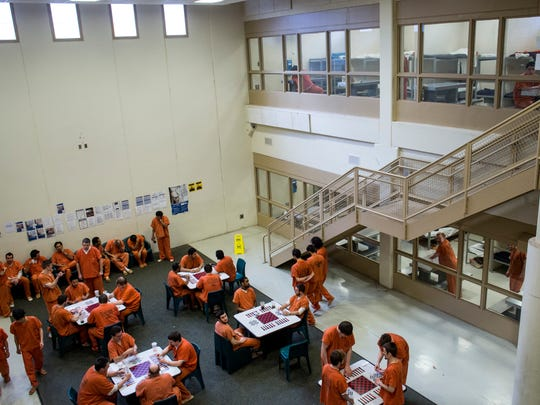 Inmates play card games and talk in the male pod at