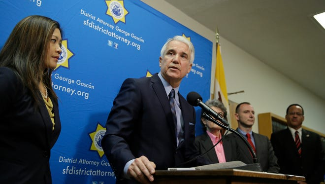 San Francisco District Attorney George Gascon, at podium, answers questions while standing with members of his staff and the Los Angeles District Attorney's office during a news conference about the ridesharing companies Uber and Lyft Tuesday, Dec. 9, 2014, in San Francisco. California prosecutors have filed a lawsuit against Uber over the ridesharing company's background checks and other allegations, adding to the popular startup's worldwide legal woes. Meanwhile, Gascon said Tuesday that Uber competitor Lyft has agreed to pay $500,000 and change some of its business practices to settle its own lawsuit. (AP Photo/Eric Risberg)