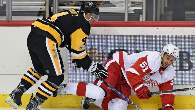 Penguins' Justin Schultz checks Red Wings' Frans Nielsen during the first period of Wednesday's preseason game.