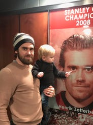 Henrik Zetterberg and his son, Love, next to a picture