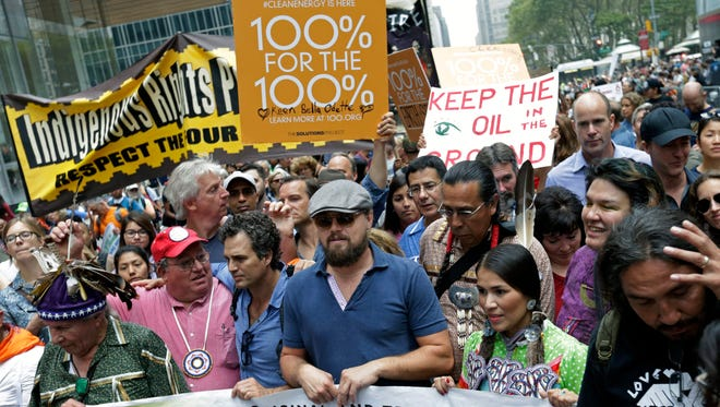 Actors Leonardo DiCaprio, center, and Mark Ruffalo, left, participate in the People's Climate March in New York City on Sept. 21, 2014.