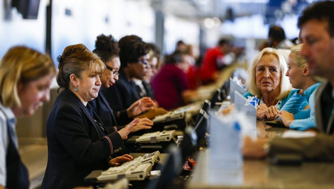 Airline agents attempt to assist passengers with their travel plans after flights were delayed or canceled at O'Hare International Airport in Chicago on Sept. 26, 2014.