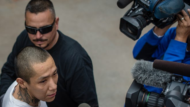 Escaped inmate Lionel Clah, bottom left, is escorted into the New Mexico State Police office in Albuquerque after being captured Saturday afternoon. Police say Clah, the second of two convicts who escaped a prison transport van, surrendered peacefully after being found in an Albuquerque apartment. The other inmate was found on Friday.